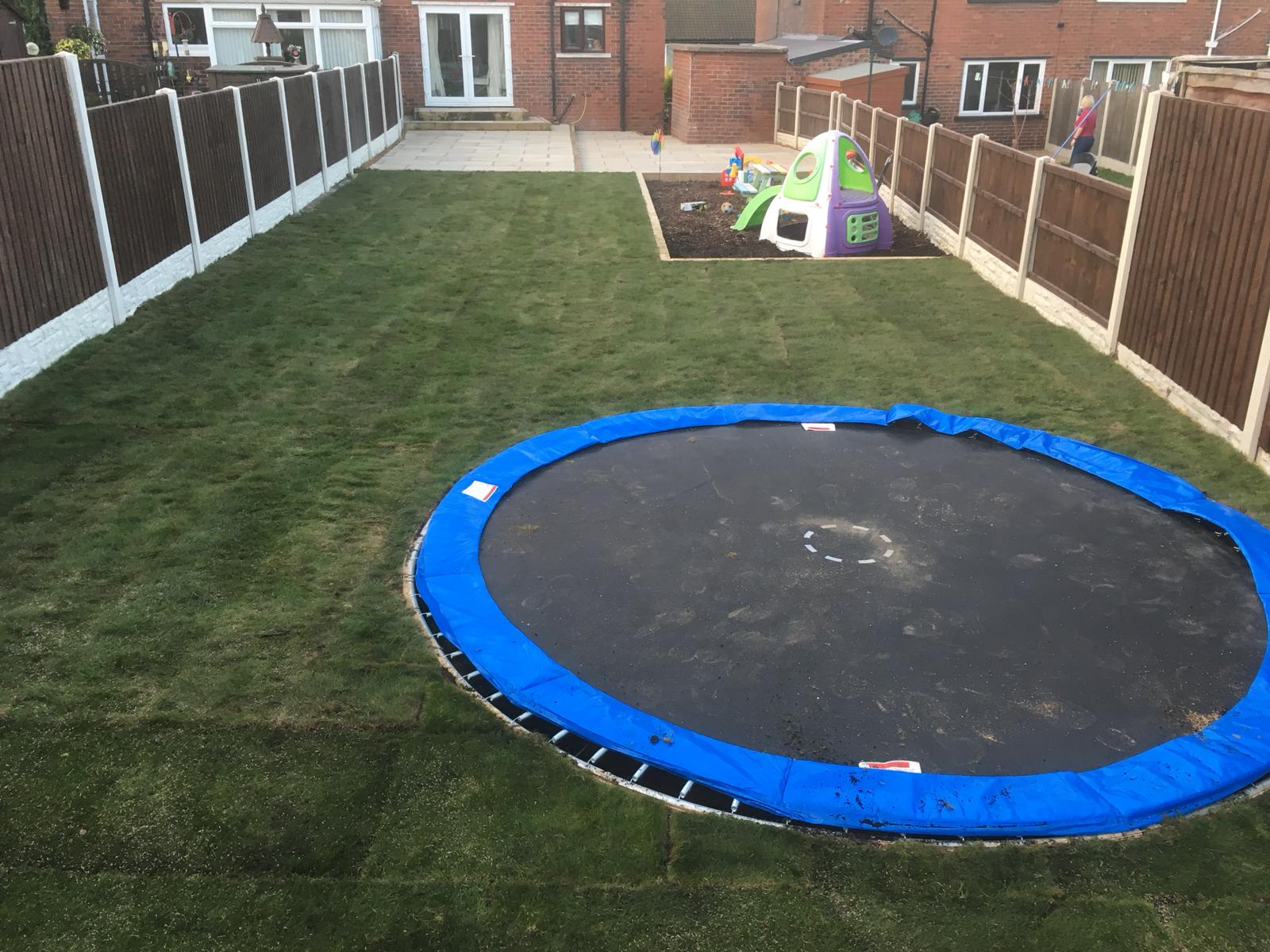 Landscaping project completed trampoline and grass